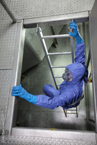 specialist in protective uniform  going up a metal ladder