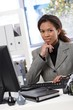 Attractive businesswoman sitting at desk in office