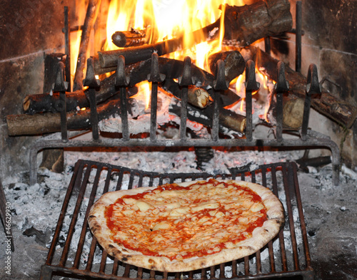 pizza margherita baked in to the fire of a fireplace in the tave