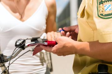 Frau auf Fahrrad mit Polizist in Kontrolle