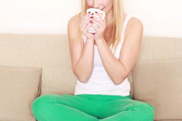 Mädchen trinkt Tee auf Sofa