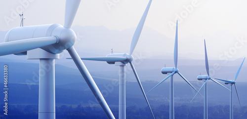 Leinwanddruck Bild Wind Turbines with distant mountains