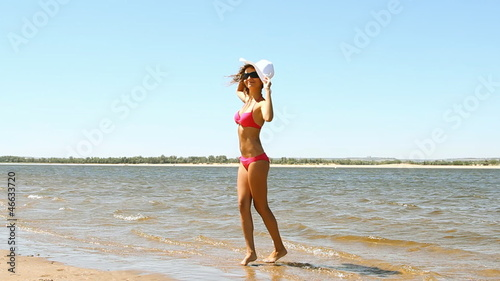 tanned young woman posing on the beach