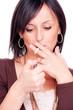 Woman lights a cigarette