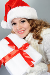 Beautiful young woman in Santa hat with present box