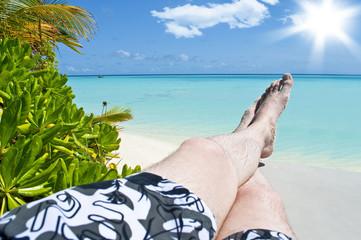 Beine auf einer Liege am Strand im indischen Ozean