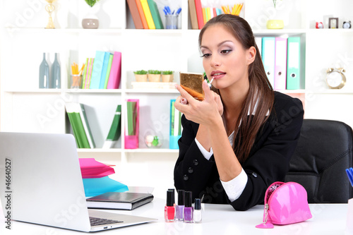 young business woman looking in the mirror and using lipstick