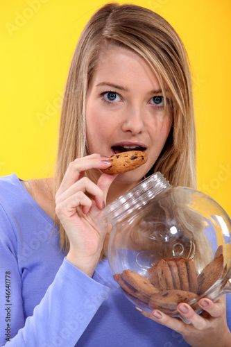 Blonde woman eating crackers