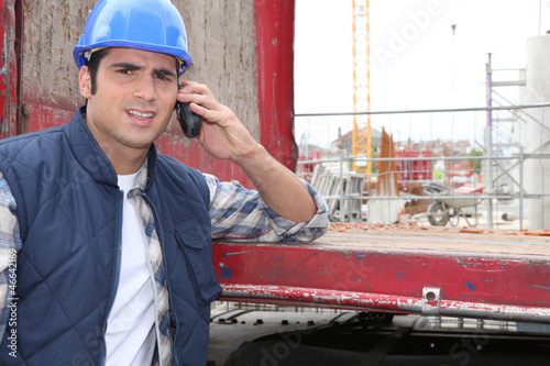 Worker leaning on red beam