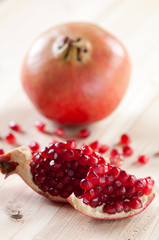 Vertical shot of a pomegranate and grains on wooden boards