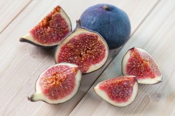 Horizontal shot of sliced fig fruits on wooden boards
