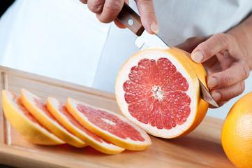 Studio shot of female hands slicing a ripe grapefruit
