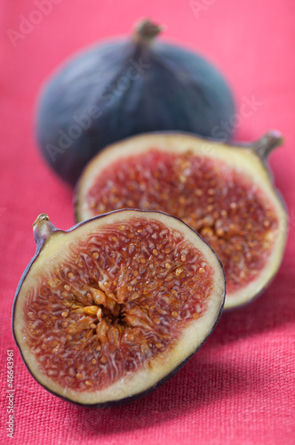 Close-up of sliced and whole fig fruits on a red serviette