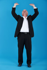 Senior businessman pushing upwards