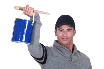 craftsman painter holding a can and a brush