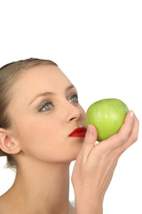 Naked woman in full makeup with a green apple