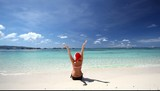 Happy woman in Santa Hat on tropical beach