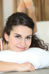 Pretty woman resting on a white pillow
