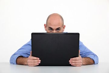 Man hiding behind his laptop