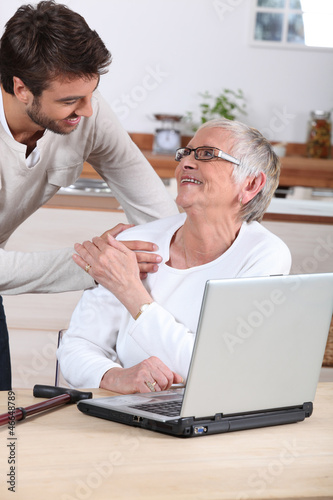 man explaining to senior woman how to use computer