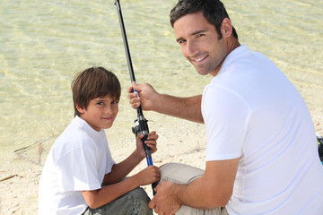 Little boy fishing with his dad