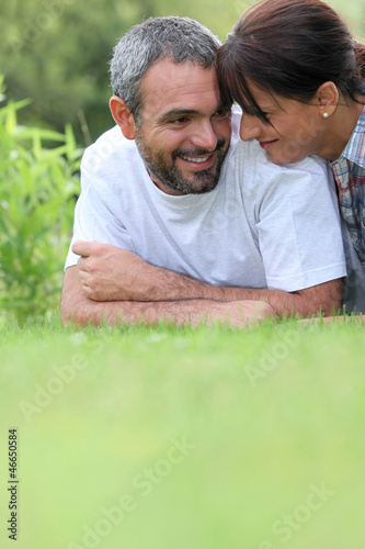 Couple laying in field