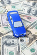 The toy car for dollar banknotes as a background