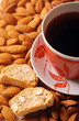 Coffee cup with biscotti on almond background