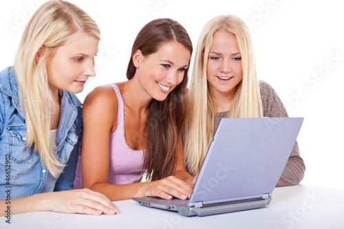 Drei attraktive junge Frauen sitzen gemeinsam vor Laptop