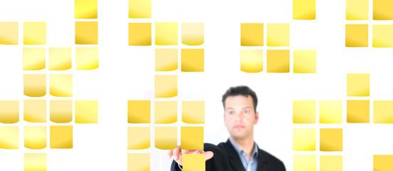 Mann ordnet Notizzettel an der Wand - Cluster
