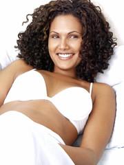 Hermosa mujer latina feliz recostada en una cama,sonriendo.