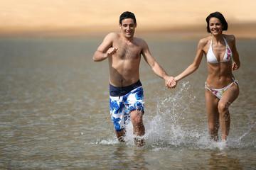 Happy couple running through the sea