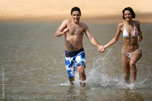 Happy couple running through the sea