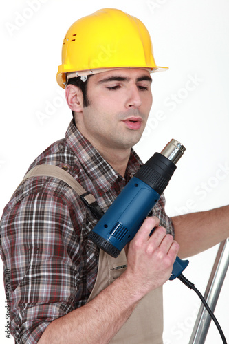 Tradesman blowing on his screw gun