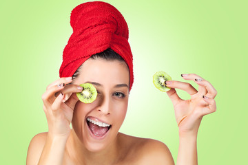 Beautiful woman with kiwi slices mask over gren background