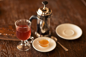 red tea with honey on wood table.