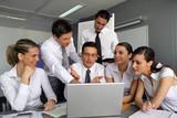 Business team gathered around laptop