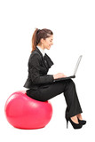 Busy woman sitting on a pilates ball and working on a notebook c