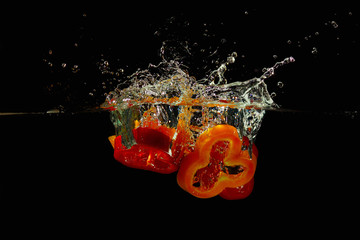 Slices of red and yellow peppers falling into the water