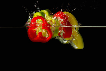 Slices of red and green peppers falling into the water