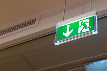 green illuminated exit sign on ceiling