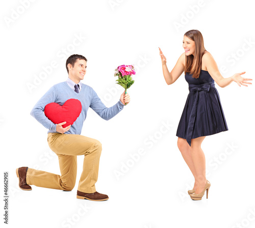 Male on knee giving a bouquet of flowers to his girlfriend