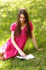 Attractive happy smiling student teen girl reading book outdoor