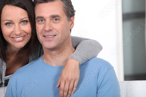 Woman hugging her husband from behind