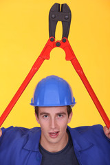 Man holding bolt-cutter over his head
