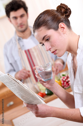 Woman drinking a glass of water and reading the paper