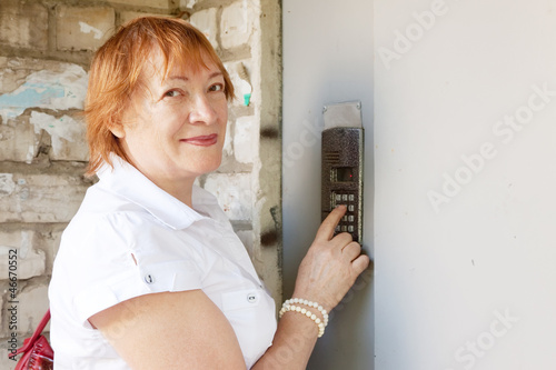 woman pushing button of house intercom