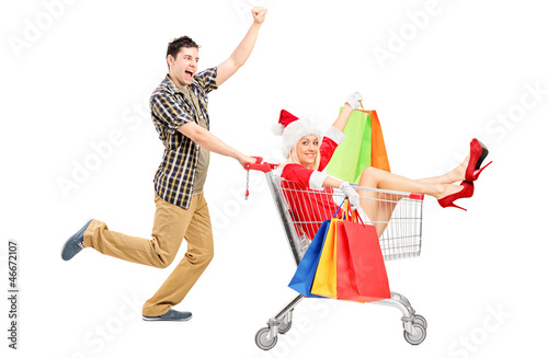 Male pushing a shopping cart and woman in christmas costume