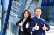 A couple of young business persons holding thumbs up