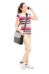 Smiling school girl with shoulder bag talking on a phone